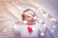 Weinig zuigeling met het stuk speelgoed van de hartvorm op borst en feeligths stock foto's