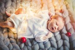 Weinig zuigeling met Kerstmis rond snuisterijen stock afbeeldingen