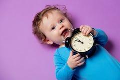 Weinig zuigelingsbaby met wekker royalty-vrije stock afbeelding