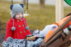 Weinig zuster die aan een babymeisje spreken in een wandelwagen Stock Fotografie