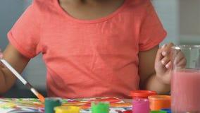 Weinig zwart meisje die een slordige tekening met kleurrijke verf, artistiek kind maken stock footage