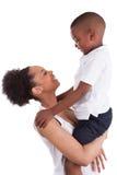 Weinig zwarte jongen met haar moeder Stock Afbeelding