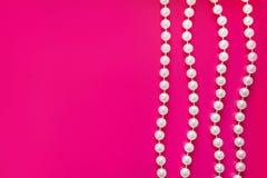 Weinigen witte parel parelen threadson een heldere roze achtergrond glamor royalty-vrije stock afbeelding
