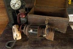 Weinleseöllampe, alte Holzkiste und Wecker auf altem hölzernem Stockbild