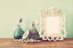 Weinlese antigue Parfümflaschen mit altem Bilderrahmen, auf Holztisch Retro- gefiltertes Bild Lizenzfreies Stockfoto