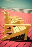 Weinlese-Art Adirondack-Stühle auf Plattform Stockbilder