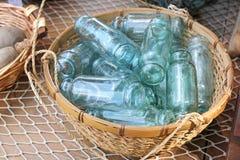 Weinlese-blaue Glasflaschen-Sammlung im Weidenkorb Stockbilder