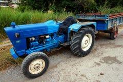 Weinlese-blauer Traktor und Anhänger Stockbild