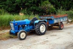 Weinlese-blauer Traktor und Anhänger Lizenzfreie Stockfotos