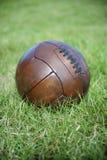 Weinlese-Brown-Fußball-Fußball-Grün-Rasenfläche Lizenzfreie Stockfotos