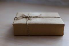 Weinlese-Brown-Geschenkbox auf hölzernem Hintergrund - filtern Sie die Verarbeitung Stockfoto