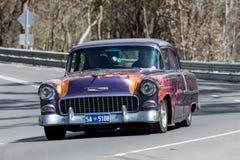 Weinlese Chevrolet, das auf Landstraße fährt stockfotos