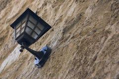 Weinlese, die Metalllaterne innerhalb des Hängens an einer alten Steinwand schaut Stockfoto