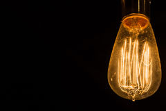 Weinlese Edison Light Bulbs, der gegen einen schwarzen Hintergrund hängt Stockfotografie