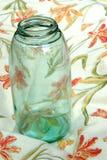 Weinlese-einmachendes Glas der Großmutter auf einem Blumengeschirrtuch Lizenzfreie Stockbilder