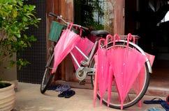 Weinlese-Fahrrad und rosa Regenschirm Stockfotografie