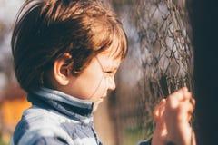 Weinlese filthered das Foto des Kindes schauend durch den Zaun Stockfotos