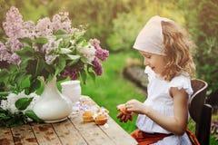 Weinlese gekleidetes Kindermädchen, das im Frühjahr Kuchen mit Blumen auf Gartenteeparty verziert lizenzfreie stockfotografie
