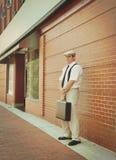 Weinlese-Geschäftsmann, der durch Backsteinmauer im Stadtzentrum gelegen steht Lizenzfreie Stockfotografie