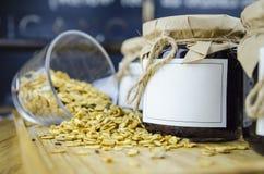 Weinlese-Glas auf hölzerner Platte und verschütteten Samen im Hintergrund Lizenzfreie Stockfotografie
