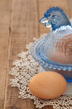Weinlese-Glashuhn mit Brown-Ei auf Holz Stockbild