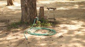 Weinlese-grüner Wasser-Schlauch und rotes Ventil im Garten unter großem Baum mit altem rustikalem hölzernem Schemel lizenzfreie stockfotografie