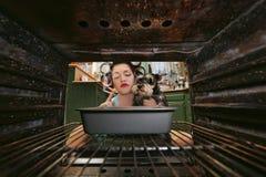 Weinlese-Hausfrau Smoking und kochen Abendessen Stockfoto