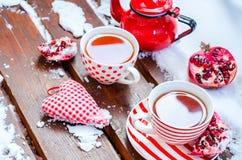 Weinlese-Herz, heiße Tasse Tee auf dem Schnee, rote Teekanne Lizenzfreie Stockbilder