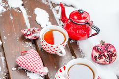Weinlese-Herz, heiße Tasse Tee auf dem Schnee, rote Teekanne Lizenzfreies Stockfoto