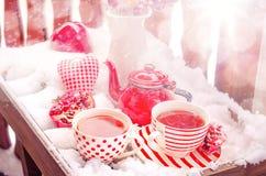 Weinlese-Herz, heiße Tasse Tee auf dem Schnee, rote Teekanne Stockbild