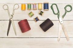 Weinlese-Hintergrund mit nähenden Werkzeugen; Scheren, Spulen von gefärbt stockfoto
