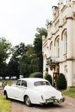 Weinlese-Hochzeits-Auto verziert mit Blumen Glückliche Paare in der Weinlesekleidung Stockfoto
