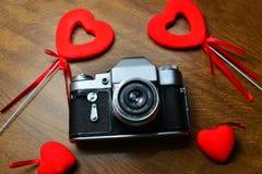 Weinlese-Kamera auf Holztisch mit roten Herzen Stockfotos
