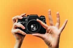 Weinlese-Kamera in der weiblichen Hand Ein Foto photograph Manueller Fokus Farbiger Hintergrund Orange stockfotografie