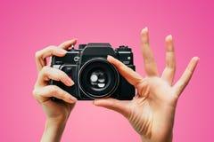 Weinlese-Kamera in der weiblichen Hand Ein Foto photograph Manueller Fokus Farbiger Hintergrund Rosa stockfotos