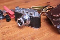 Weinlese Kamera und accesoriess auf hölzernem Hintergrund Lizenzfreies Stockbild