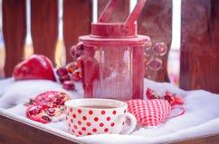 Weinlese-Kerzen-Lampe mit Herzen, heiße Tasse Tee auf dem Schnee Stockfoto