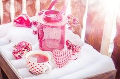 Weinlese-Kerzen-Lampe mit Herzen, heiße Tasse Tee auf dem Schnee Lizenzfreies Stockbild