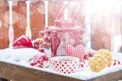 Weinlese-Kerzen-Lampe mit Herzen, heiße Tasse Tee auf dem Schnee Stockfotografie