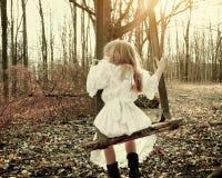 Weinlese-Kind, das auf altem Schwingen im Holz allein sitzt Lizenzfreies Stockfoto