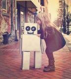 Weinlese-Kind, das draußen Roboter-Freund umarmt stockbild