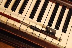 Weinlese-Klavier und Violinenbogen Stockfotografie