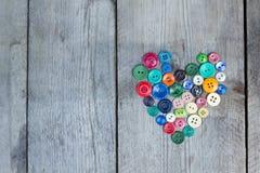 Weinlese knöpft in Form eines Herzens auf einem hölzernen Hintergrund Stockfoto