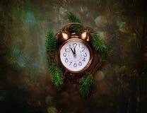 Weinlese-kupferner Wecker fünf Minuten zu den neue Jahr-Count-down-Weihnachtskranz-Tannen-MitternachtsBaumasten auf schwarzem Hin Lizenzfreies Stockfoto