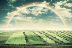 Weinlese-Landschaft mit Feldern und Regenbogen Stockfotografie