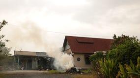 Weinlese-Landschafts-Haus mit brennendem Stapel des Strohs im Garten stockbild