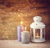 Weinlese-Laterne mit brennenden Kerzen auf Holztisch und Funkeln beleuchtet Hintergrund Gefiltertes Bild Lizenzfreies Stockfoto