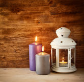 Weinlese-Laterne mit brennender Kerze auf Holztisch Gefiltertes Bild Stockbild