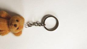 Weinlese-Metall Keychain mit Teddy Bear auf Papierbeschaffenheit stockfotografie