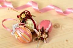 Weinlese-Ostern-Dekoration von drei rosa farbigen Ostereiern verziert mit glänzenden Bändern stockbilder